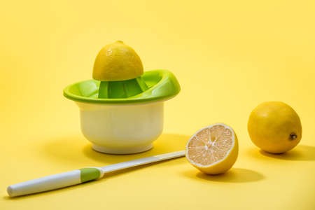Squeezed Lemon on a Manual HandHeld Citrus juicer over colorful Yellow background
