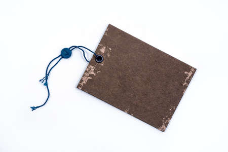 Empty brown paper tag tied with black string. Price tag, gift tag, sale tag on the blue background, close up