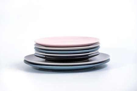 Stack of seven Large and Small colorful empty plates isolated on white background, side view. Navy Blue, Grey, Black, White, and Pink empty plates collection