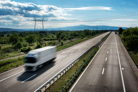 Transportation Truck in high speed on a highway through rural landscape. Fast blurred motion drive on the freeway. Freight scene on the motorway 스톡 콘텐츠