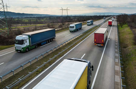 Convoys or caravans of transportation trucks passing on a highway on a bright blue day. Highway transit transportation with white and red lorry trucks
