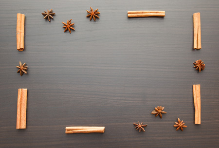 string together: wooden background with star anise and cinnamon sticks