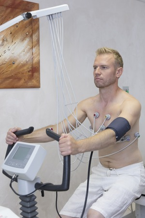 doctor with electrocardiogram equipment making cardiogram under load test to male patient in hospital clinic