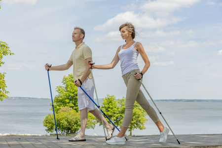 Young couple hiking in the nature nordic walking
