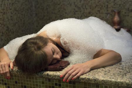 Young woman in hammam or turkish bath soap foam.