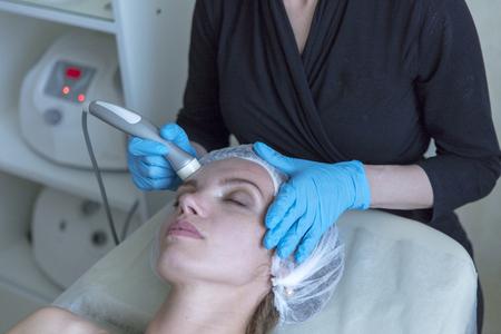 Beautiful woman in professional beauty salon during photo rejuvenation procedure Stock Photo