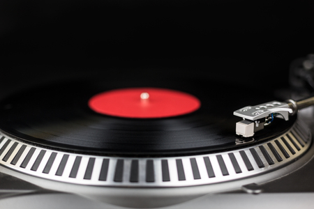 Professional party djs turntable. Analog stage audio equipment for concert in nightclub. Play mix music tracks on vinyl records. Turntables needle cartridge scratches vinyl disc. DJ setup for festival with red on black background Foto de archivo - 106621717