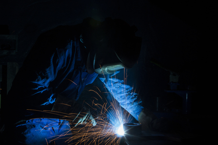 Industrial Worker in dark at the factory welding closeup