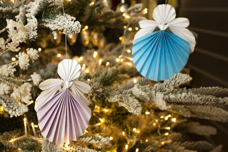 New Year handmade pastel angel papercraft origami figures on christmas tree with holiday interior decorations with warm lights. Christmas concept winter card studio shot close-up