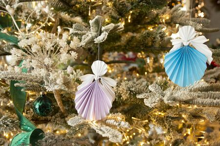 Nice New Year handmade angel papercraft origami figures on christmas tree with holiday interior decorations with warm lights. Christmas concept winter card studio shot close-up