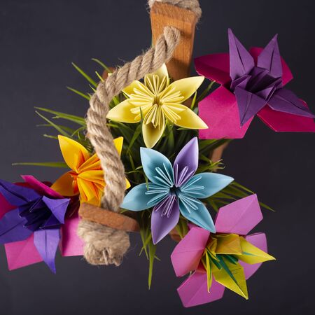 Handmade colored paper flowers origami bouquet paper craft art in a basket with grass in the studio on blackbackground