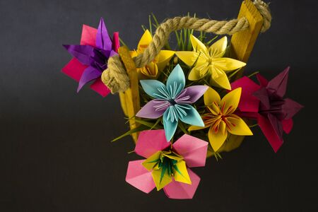 Handmade colored paper flowers origami bouquet paper craft art in a basket with grass in the studio on colored background topshot