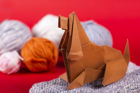 craft origami concept of a cozy home - a dog with balls of wool sits on a lash. Handmade art paper close up studio shot.