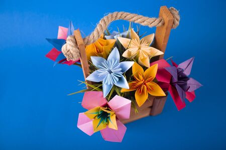 Handmade colored paper flowers origami bouquet paper craft art in a basket with grass in the studio on colored blue background