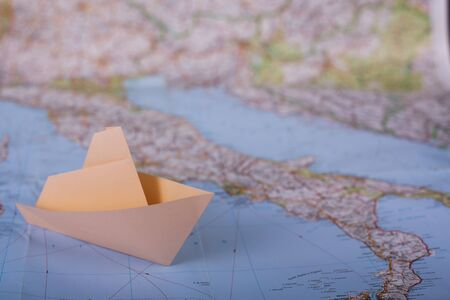 Travel holiday vacation concept origami handmade tourist papercraft paper ship on map near italy close up studion shot