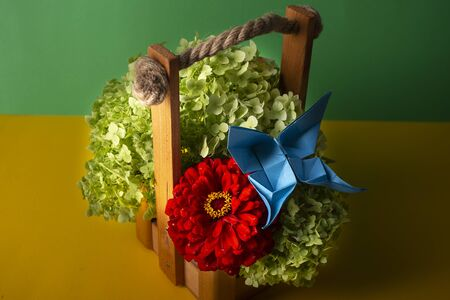 origami butterfly on red flower with a green bush in a basket on a colored background handcrafted handmade art beautiful bouquet studio close shot 写真素材