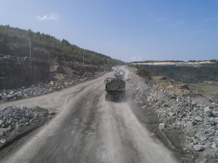 Huge industrial dump truck in a stone quarry road loaded transporting marble or granite shot from a drone 写真素材