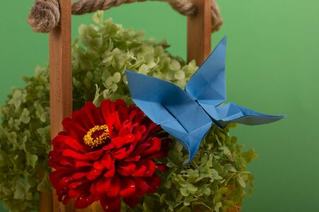handmade art origami butterfly on a green bush in a basket on a colored background beautiful bouquet studio close shot 写真素材