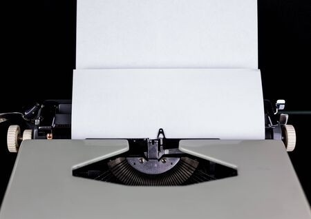 Typewriter on the table on a black background with white paper with empty space. Workplace of the writer or author. Idea Concept.