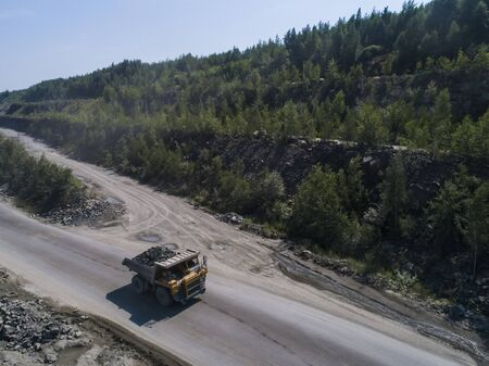 Huge industrial dump truck in a stone quarry loaded transporting marble or granite shot from a drone in nature 写真素材