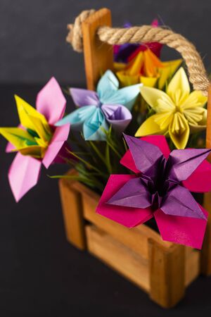 Handmade colored paper flowers origami bouquet paper craft art in a basket with grass in the studio on colored background closeup macro 写真素材