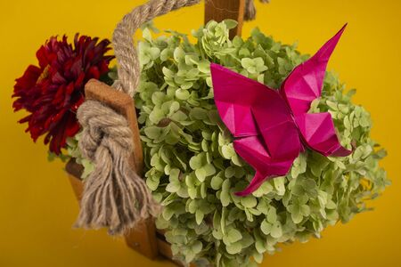 origami butterfly on a green bush art handmade in a basket on a colored background beautiful bouquet studio close shot