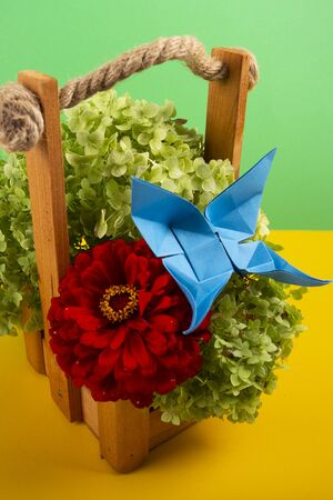 origami butterfly on a green bush in a basket on a colored background beautiful bouquet studio close shot with red rose 写真素材