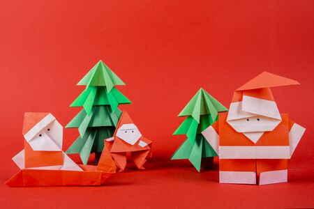 New Year card handmade origami santa claus figures with trees. Christmas concept winter crafted decorations studio shot on red background close up 写真素材