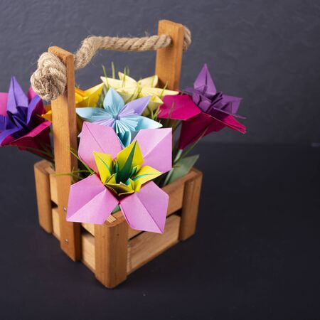 Handmade colored paper flowers origami bouquet paper craft art in a basket with grass in the studio on colored background macro