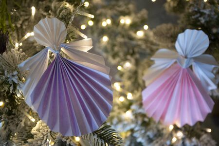 Traditional New Year handmade angel papercraft origami figures on christmas tree with holiday interior decorations with warm lights. Christmas concept winter card studio shot close-up