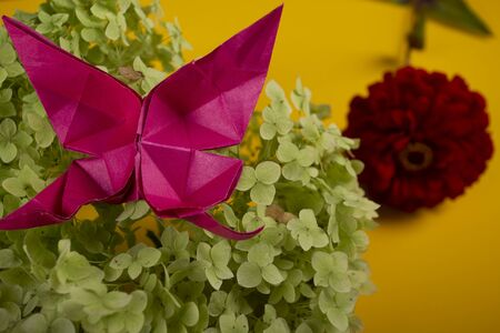origami butterfly on a green bush in a basket on a colored background beautiful bouquet studio close shot handmade crafted art 写真素材