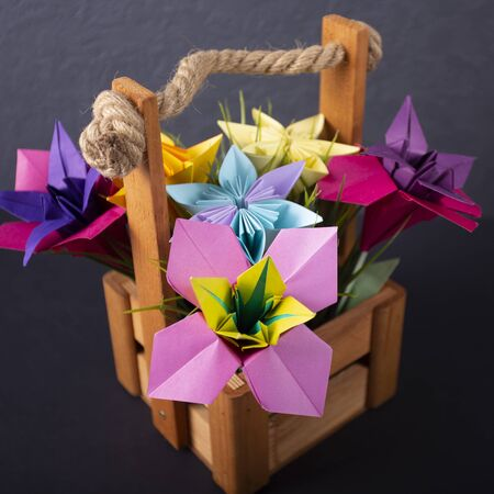 Macro Handmade colored paper flowers origami bouquet paper craft art in a basket with grass in the studio on colored background