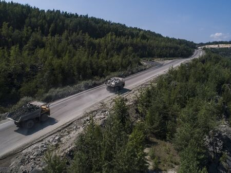 Huge industrial dump truck in a stone quarry loaded transporting marble or granite shot from a drone chase