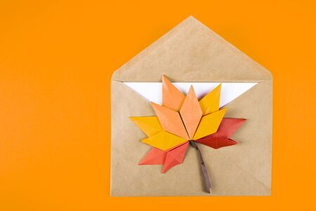Origami papercraft autumn concept fallen leaves letter in an envelope on a plain background craft art 写真素材