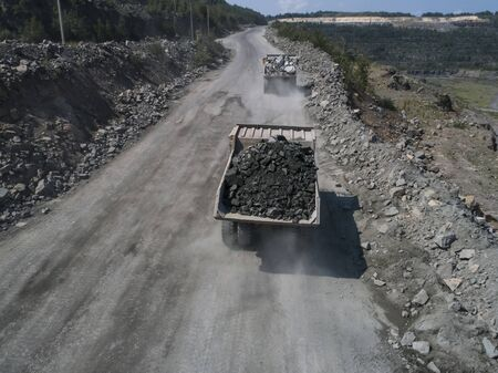 Huge industrial dump truck in a stone quarry loaded transporting marble or granite shot from a drone top shot