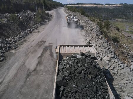 Huge industrial dump truck in a stone quarry in a quarry loaded transporting marble or granite shot from a drone Stockfoto