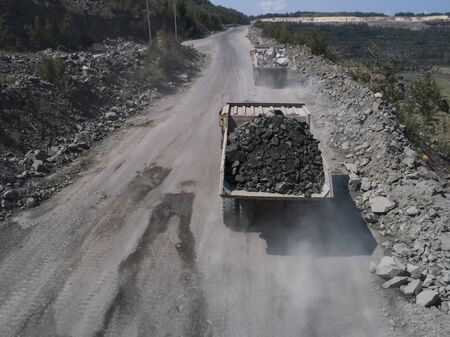 Huge on road industrial dump truck in a stone quarry loaded transporting marble or granite shot from a drone