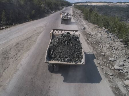 Huge industrial dump truck in a stone quarry loaded transporting marble or granite shot from a drone by quarry