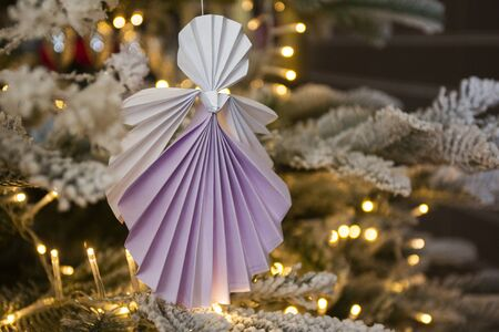 New Year handmade angel papercraft origami figures on christmas tree with holiday interior decorations with warm lights. Christmas concept winter card studio shot close-up macro Stok Fotoğraf