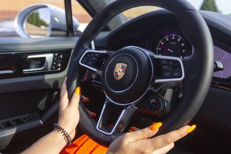 Slovenia ljubljana, 31 August 2019 - Woman hands on steering wheel of Porsche Cayenne Coupe Turbo S from Stuttgart during test drive car interior shot close-up