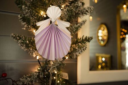 New Year handmade angel papercraft origami figures on christmas tree with holiday interior decorations with warm lights. Christmas concept winter xmas card studio shot close-up