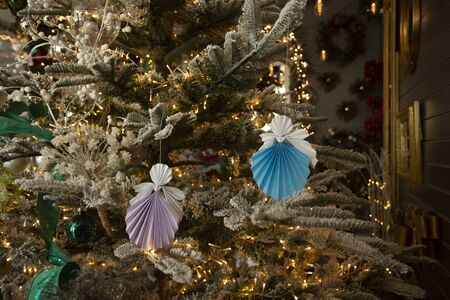 Colored New Year handmade angel papercraft origami figures on christmas tree with holiday interior decorations with warm lights. Christmas concept winter card studio shot close-up