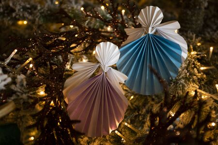 New Year handmade angel papercraft origami figures on christmas tree with holiday interior decorations with warm lights. Christmas winter card studio shot close-up