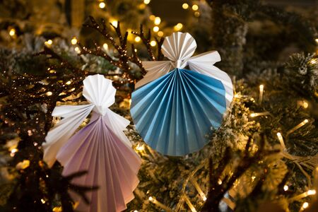 New Year handmade angel papercraft origami figures on christmas tree with holiday interior decorations with warm lights and snow. Christmas concept winter card studio shot close-up Stok Fotoğraf