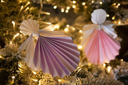 New Year handmade angel origami figures on christmas tree with holiday interior decorations with warm lights. Christmas concept winter card studio shot close-up Stok Fotoğraf