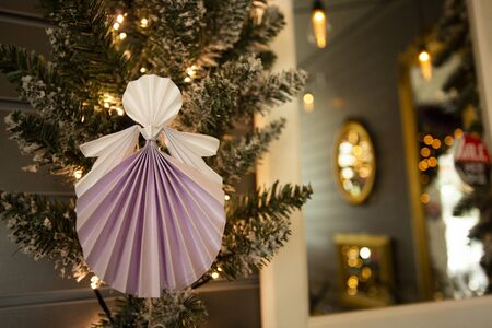 New Year xmas handmade angel papercraft origami figures on christmas tree with holiday interior decorations with warm lights. Christmas concept winter card studio shot close-up
