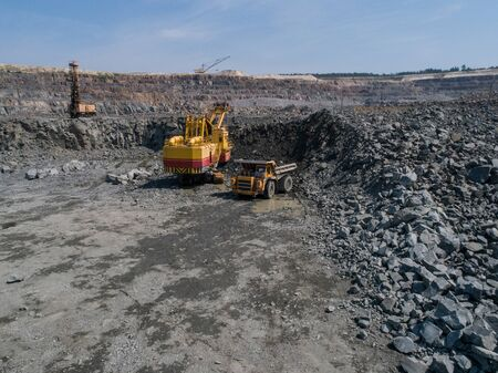 Huge industrial dump truck in a stone quarry loaded transporting marble or granite shot