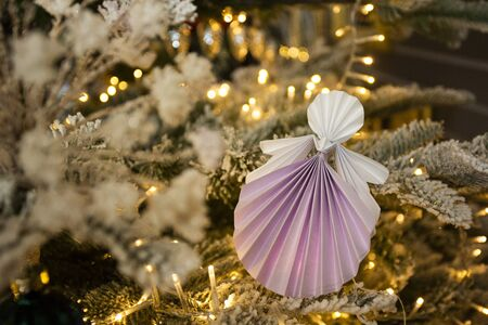 New Year handmade angel papercraft origami figures on christmas tree with holiday interior decorations with warm lights. Christmas snow tree concept winter card studio shot close-up