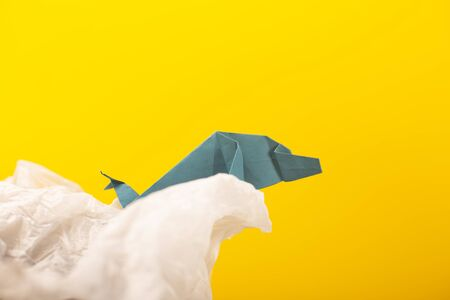 whale on a wave handmade origami craft paper art on a yellow paper background 写真素材
