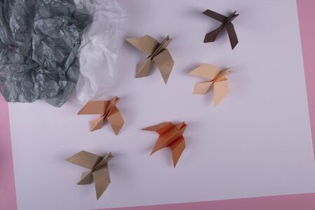 Migration of birds concept of autumn handmade origami birds fly away from the cold on a paper background 写真素材